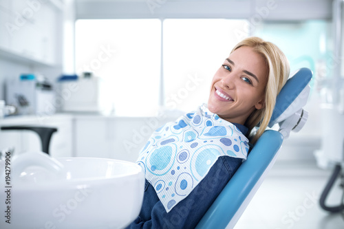 Smiling and satisfied patient in a dental office