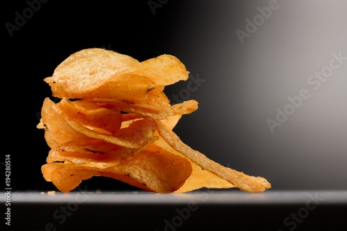 Fotografía  Kartoffel Chips gestapelt im Spotlight - vor schwarzem Hintergrund