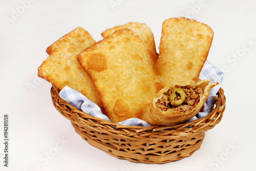 Brazilian typical pastry called pastel in white background with one of meat open