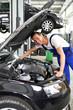 freundlicher KFZ Mechaniker untersucht Motor eines Autos in einer Werkstatt // friendly car repair men check the engine in car workshop