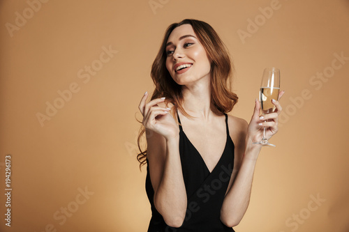 Slika na platnu Young happy woman looking away and smiling with champagne