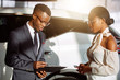 african Car dealer showing vehicle to black woman