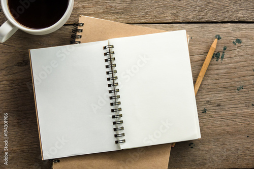 Obraz Top view of blank notebook with white coffee and natural light on wooden table. - fototapety do salonu
