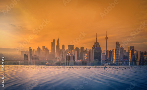Fotografie, Obraz  Cityscape of Kuala lumpur city skyline with swimming pool on the roof top of hotel at sunrise in Malaysia