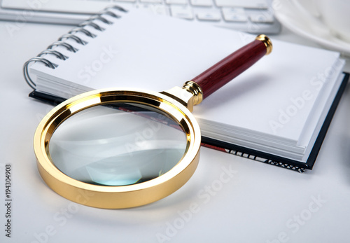 large magnifying glass lies on a notebook on the desktop