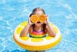 Child in swimming pool. Kid eating orange.