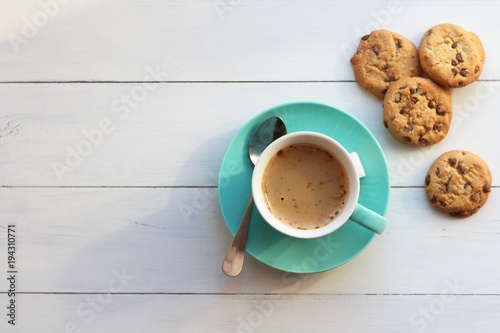 Coffee in a turquoise mug and cookies on a white table the top view