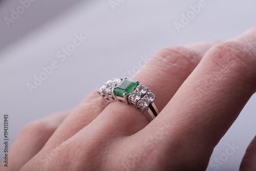 Vászonkép Dedo corazón con anillo de esmeralda y diamantes