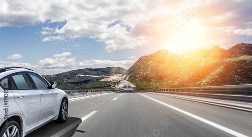 Fototapeta A white car rushing along a high-speed highway in the sun. obraz