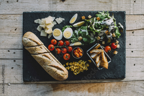 Overhead view of food on slate over wooden table