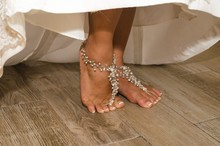 Pearls Anklet On Bride's Feet With Wedding Dress. Woman Getting Ready For Ceremony