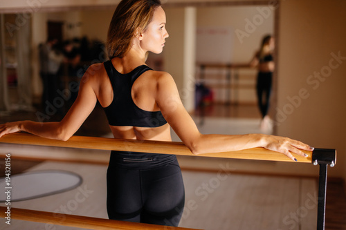 Beautiful woman dancer posing near barre in ballet studio.