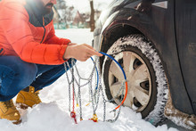Man Putting Snow Chains On Car...