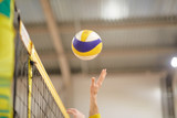 The volleyball player's hand in the covered gym fights the ball in front of the net,