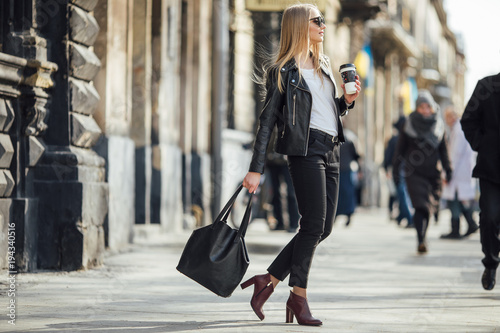 Photo Young pretty girl walk on the street with cup of coffee on her hand and wear sun