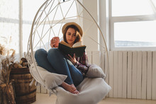 Girl Relaxes Reading A Book An...