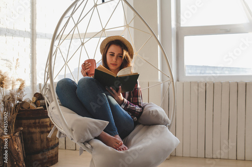 Valokuva Girl relaxes reading a book and drinks tea.