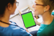 Rear View Of Professional Middle Aged Nurse Holding A Tablet With Blank Editable Green Screen In A Doctors Office With Woman Patient In Front.