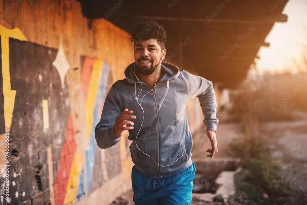Fototapeta Portrait of active motivated afro-american young attractive athletic man with earphones running inside of the abandoned place. - obraz na płótnie