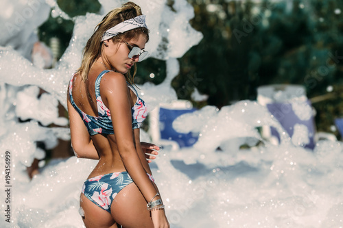 Fotografie, Obraz  Cute young woman in glasses posing and raised her hands at a foam party at the beach