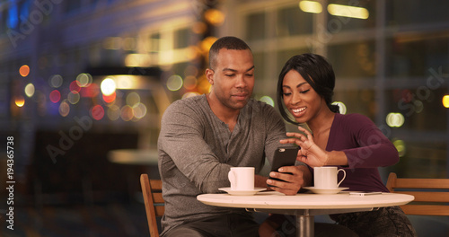 Valokuva  Happy Black couple using smart phone in coffee shop at night