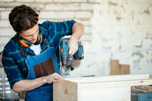 Fototapeta Carpenter drills a hole with an electrical drill obraz na płótnie