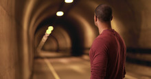 African American Stares Down A Tunnel. A Black Man Looks For A Light At The End Of The Tunnel