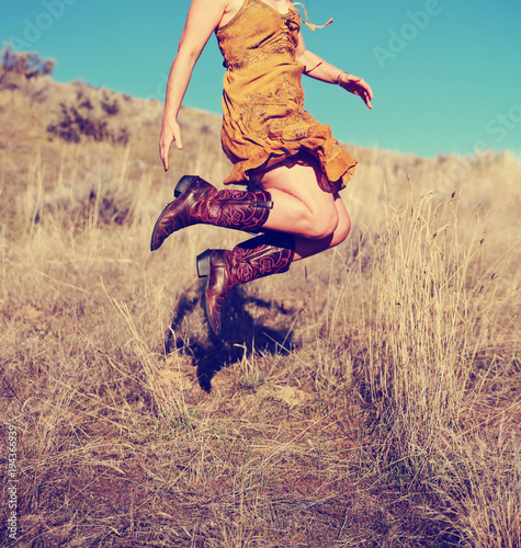 Fotografia, Obraz  pretty woman in a skirt jumping up in cowboy boots in a wheat field on a hot sum