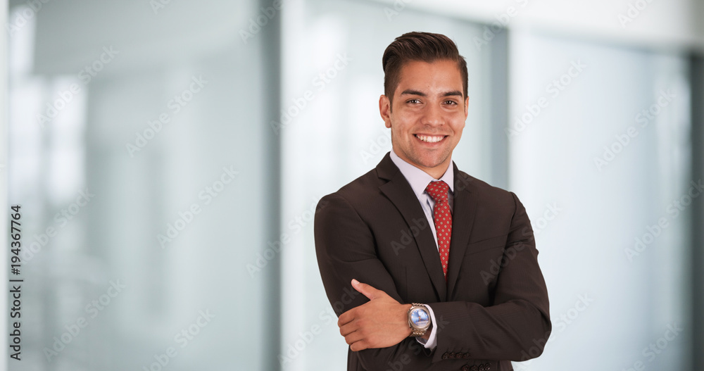 Fototapeta Happy smiling young Hispanic businessman standing in office with arms crossed looking at camera. Copyspace or copy space next to business professional with smile on his face