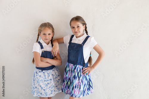 Two girls in fashionable clothes on the background of a textured wall Wallpaper Mural