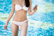 Women wearing bikinis are using the phone. Swimming pool