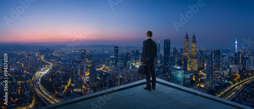 Fotografia  Businessman stand at rooftop looking great cityscape view and thinking business plan of the future