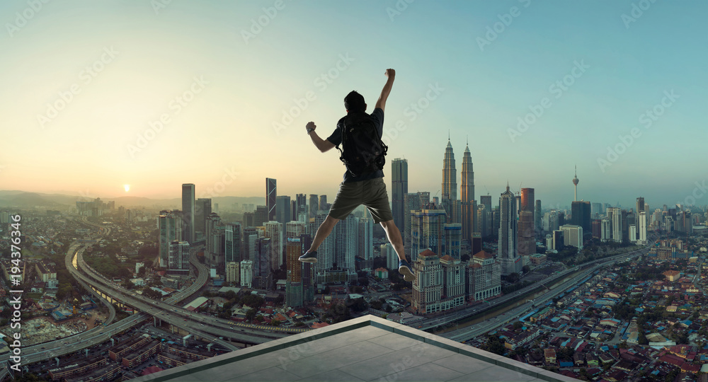 Fototapeta Young man jumping on rooftop with great cityscape sunrise view.