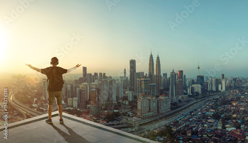 Young man stand at rooftop looking great cityscape sunrise view and praying Canvas