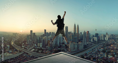 Fotografie, Obraz  Young man jumping on rooftop with great cityscape sunrise view.