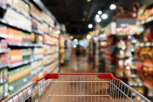 Cuadros en Lienzo Shopping cart with supermarket aisle blur abstract background