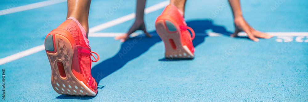 Fototapeta Sprinter waiting for start of race on running tracks at outdoor stadium. Sport and fitness runner woman athlete on blue run track with orange running shoes. Panorama banner.