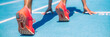 canvas print picture - Sprinter waiting for start of race on running tracks at outdoor stadium. Sport and fitness runner woman athlete on blue run track with orange running shoes. Panorama banner.