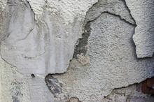 Abfallender Putz Mit Rissen In Mehreren Schichten An Hausmauer Sanierungsbedarf, Sloping Plaster With Cracks In Several Layers On House Wall Renovation Needs