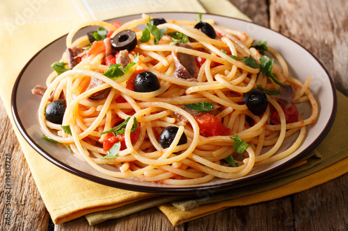 Fotografia Delicious spaghetti alla putanesca with anchovies with vegetables and greens close-up