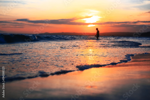 Spoed Foto op Canvas Zee zonsondergang A man walking on the beach