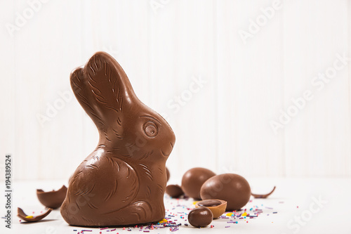 Easter chocolate bunny and eggs on white wooden background
