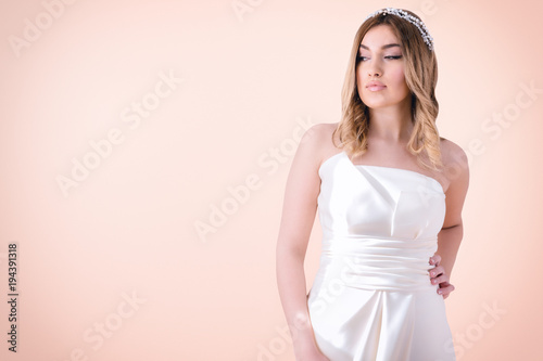 Fotografie, Obraz  Beautiful woman posing in wedding dress, isolated on light pink / orange background