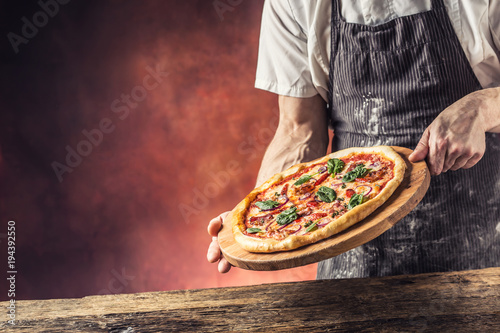 Chef and pizza. Chef offering pizza in hotel or restaurant Canvas Print