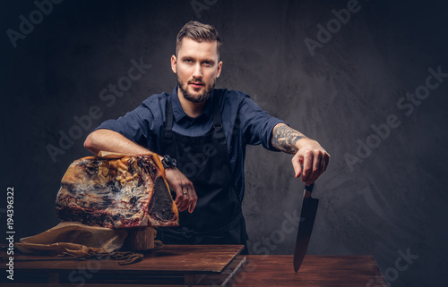 Fotografie, Obraz  Professional butcher holds a knife standing with raw smoked meat