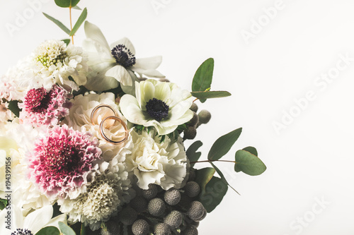 Obraz na plátně close up view of wedding rings in bridal bouquet isolated on white