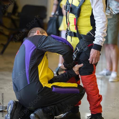 Fotografie, Obraz  Skydiver Instructor Helps Apprentice to Tie Security Belt on His Parachutist Sui