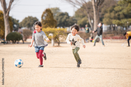 公園でサッカーをする子供