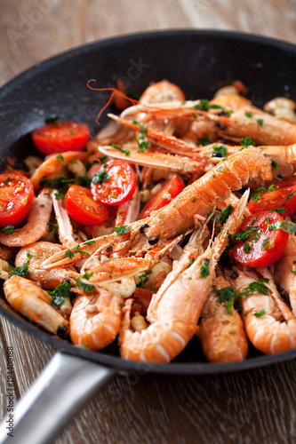 Fotobehang Schaaldieren Scampi cooked with tomatoes and parsley
