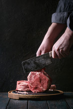 Man's Hands Cutting Raw Uncook...